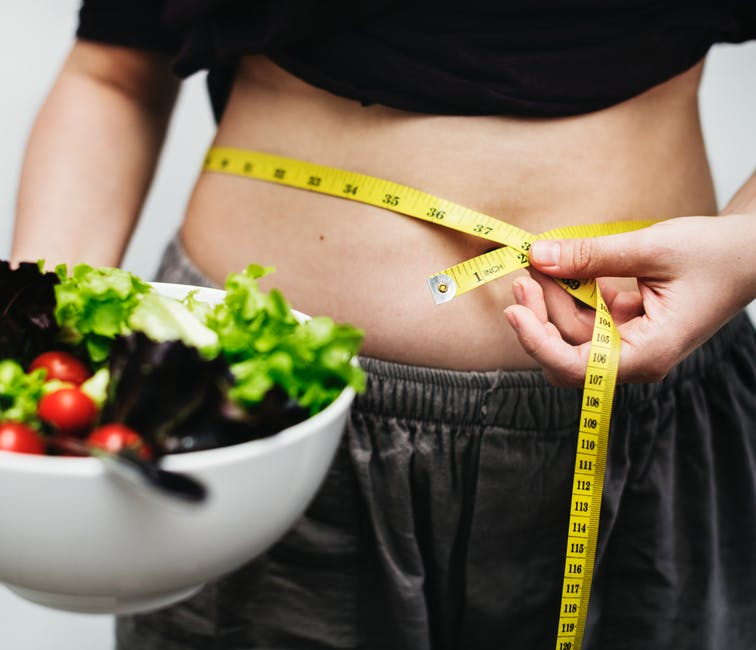 person with tape measure around waist and salad